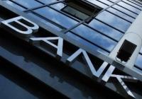 Deprecierea activelor a tăiat o treime din profitul bancherilor